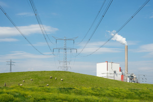 Field landscape with electric pylon and coal fired power stationの写真素材 [FYI03588979]