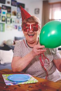 Senior woman waving balloons at birthday partyの写真素材 [FYI03589291]