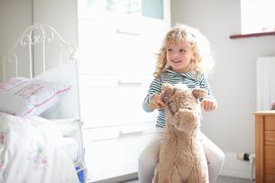Little girl on rocking horse in bedroomの写真素材 [FYI03589297]
