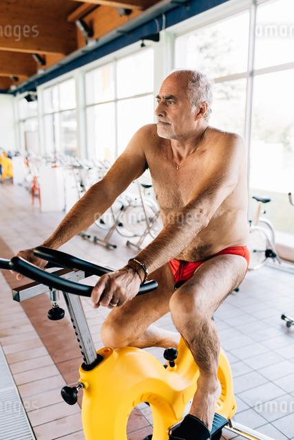 Senior man on exercise bike in gymの写真素材 [FYI03589349]