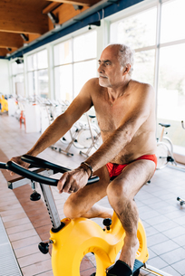 Senior man on exercise bike in gymの写真素材 [FYI03589349]