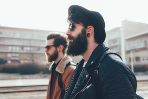 Side view of two young male hipster friends wearing sunglasses in city housing estateの写真素材 [FYI03589430]