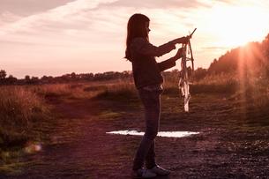 Teenage girl preparing kite on dirt track at sunsetの写真素材 [FYI03589499]