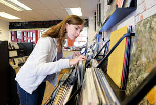 Young woman looking at stacked vinyl records in record storeの写真素材 [FYI03589511]