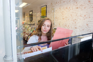 Young woman looking at vinyl records in record storeの写真素材 [FYI03589512]