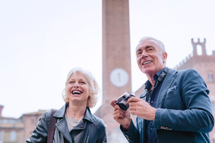 Tourist couple with digital camera in town square, Siena, Tuscany, Italyの写真素材 [FYI03589516]
