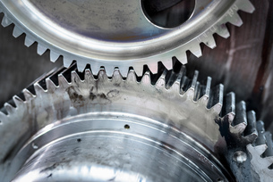 Close up detail of driver wheels with cogs of locomotive engine in train worksの写真素材 [FYI03589611]