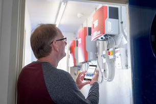 Community worker using smartphone app to check heat pump energy controlsの写真素材 [FYI03589675]