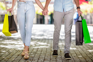 Young couple outdoors, holding hands, holding shopping bags, low sectionの写真素材 [FYI03589719]