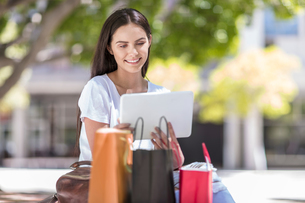 Young woman sitting outdoors, using digital tablet, shopping bags beside herの写真素材 [FYI03589721]