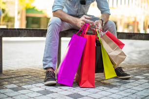 Young man sitting on bench, holding colourful shopping bags, low sectionの写真素材 [FYI03589724]