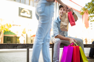 Young man sitting on bench, holding colourful shopping bags, young woman passing him more bags, lowの写真素材 [FYI03589725]