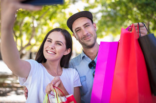 Young couple outdoors, holding colourful shopping bags, taking selfie, using smartphoneの写真素材 [FYI03589726]