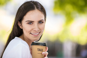 Portrait of young woman, outdoors, holding takeaway coffee cupの写真素材 [FYI03589727]