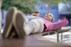 Young man outdoors, lying on bench, holding takeaway coffee cupの写真素材 [FYI03589731]