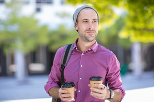 Young man outdoors, holding two takeaway coffee cupsの写真素材 [FYI03589732]