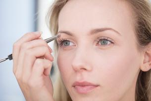 Young woman applying eyeshadow, close-upの写真素材 [FYI03589747]