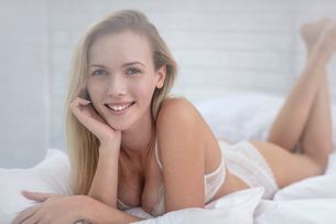 Portrait of young woman lying on bed, wearing underwearの写真素材 [FYI03589749]