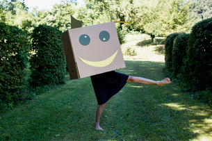 Girl with smiley face box over headの写真素材 [FYI03589830]