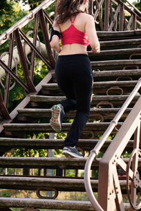 Young female runner running up stairwayの写真素材 [FYI03589882]