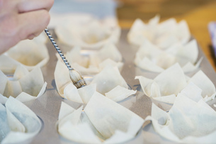 Chef placing filo pastry into baking tray, close-upの写真素材 [FYI03590022]