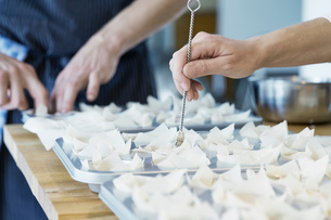 Chef placing filo pastry into baking tray, close-upの写真素材 [FYI03590023]