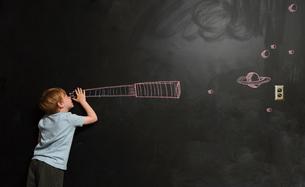 Boy looking through imaginary telescope drawn on blackboardの写真素材 [FYI03590144]