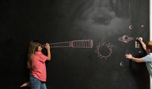 Girl looking through imaginary telescope drawn on blackboardの写真素材 [FYI03590146]