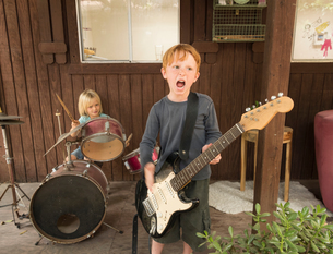 Children playing guitar and drums in bandの写真素材 [FYI03590154]