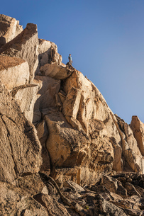 Male mountaineer looking out from top of rugged rock face, Andes, Nahuel Huapi National Park, Rio Neの写真素材 [FYI03590193]