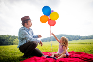 Girl sitting with father pointing up to bunch of colourful balloons in rural fieldの写真素材 [FYI03590355]