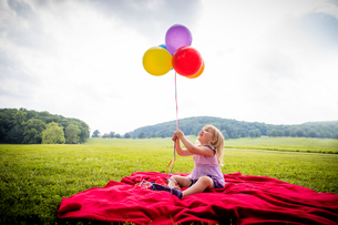Girl sitting on red blanket in rural field looking up at bunch of colourful balloonsの写真素材 [FYI03590356]