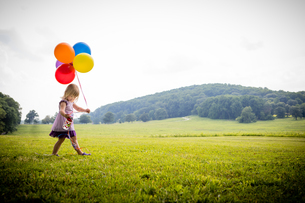 Girl walking in rural field with bunch of colourful balloonsの写真素材 [FYI03590358]