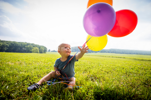 Baby boy sitting in rural field with bunch of colourful balloonsの写真素材 [FYI03590359]