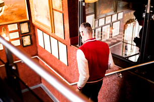 Man going down stairs in bar and restaurant, Bournemouth, Englandの写真素材 [FYI03590477]