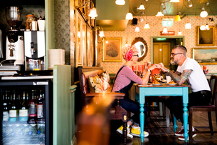 Quirky couple relaxing in bar and restaurant, Bournemouth, Englandの写真素材 [FYI03590489]