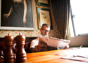 Quirky man reading newspapers in bar and restaurant, Bournemouth, Englandの写真素材 [FYI03590506]