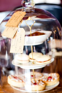 Home made cakes for sale under a glass cloche on tea room counterの写真素材 [FYI03590566]