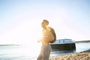 Young man training wearing backpack on sunlit beachの写真素材 [FYI03590583]