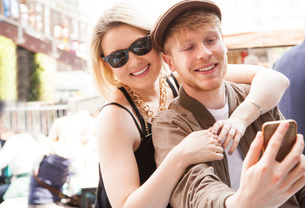 Young couple, outdoors, taking selfie, using smartphoneの写真素材 [FYI03590609]
