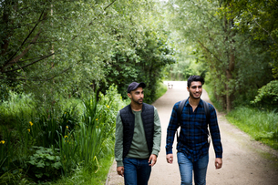 Friends walking on pathway in parkの写真素材 [FYI03590685]