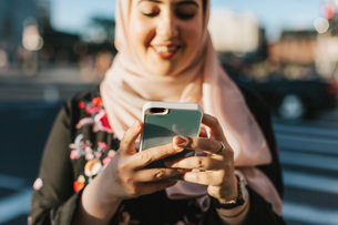Young woman wearing hijab looking at smartphone smilingの写真素材 [FYI03590772]