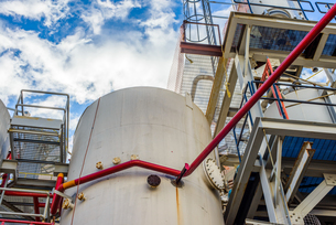 Low angle view of storage tanks and industrial piping at biofuel plantの写真素材 [FYI03590804]