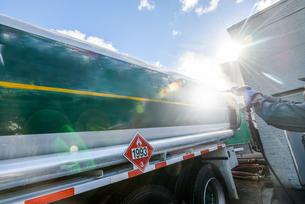 Worker pressure hosing biofuel oil tanker at sunlit biofuel plantの写真素材 [FYI03590811]