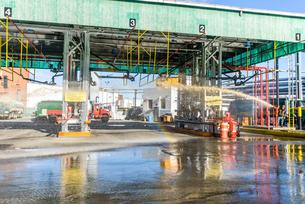 Worker pressure hosing biofuel oil tanker cleaning station at biofuel plantの写真素材 [FYI03590816]
