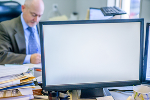 Blank computer monitor with man working in backgroundの写真素材 [FYI03590829]