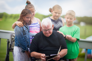 Grandfather surrounded by grandchildren giving him greeting cardの写真素材 [FYI03590924]
