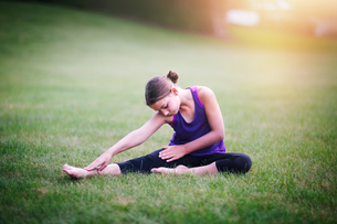 Girl stretching on grassの写真素材 [FYI03590933]