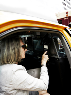 Senior businesswoman in back of taxi, making payment for journey with payment machineの写真素材 [FYI03591056]