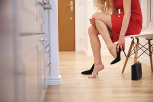 Cropped view of young woman putting on high heeled shoesの写真素材 [FYI03591128]